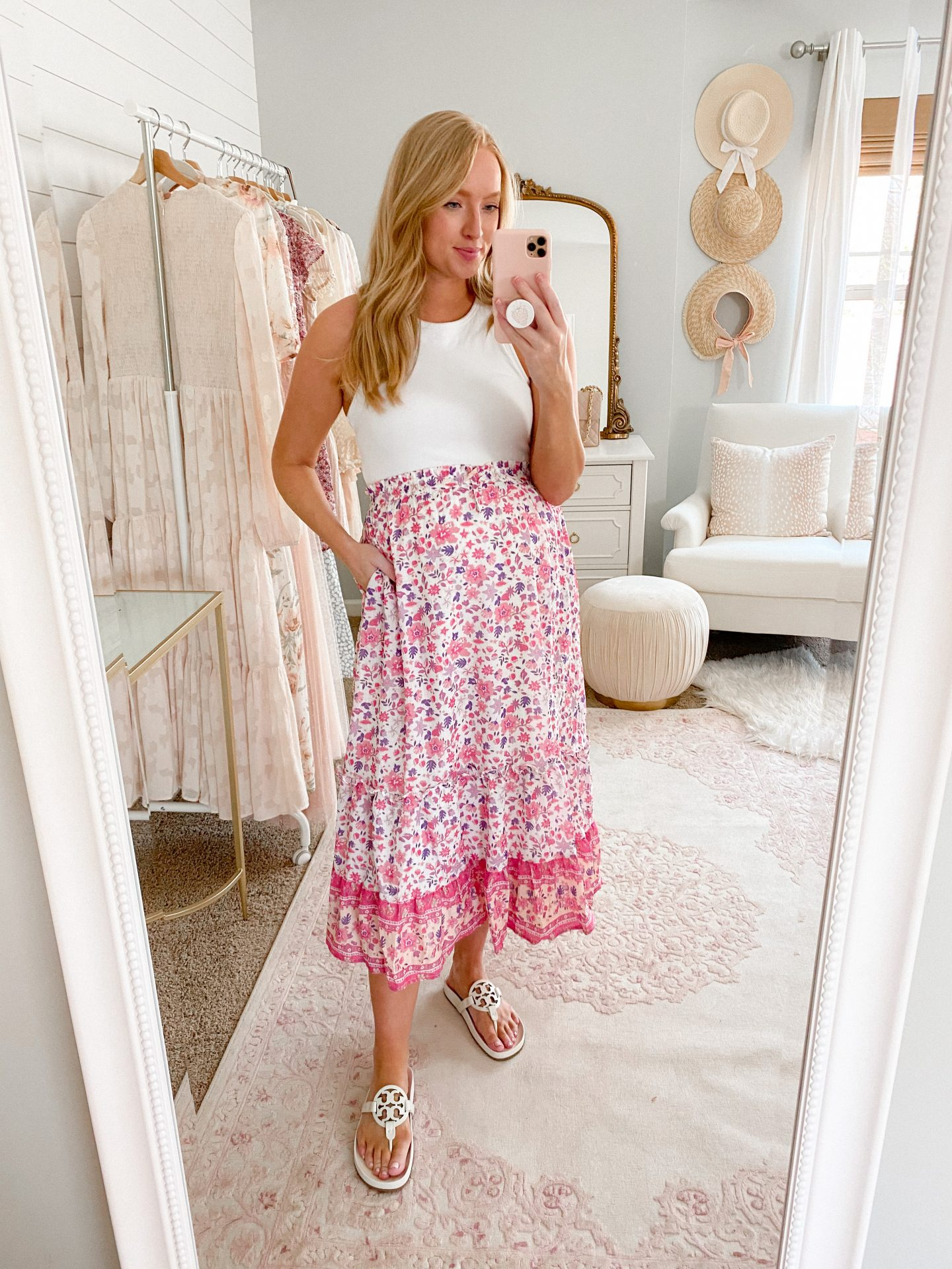 woman wearing a white top, floral pink skirt, and Tory Burch Miller Cloud Sandals