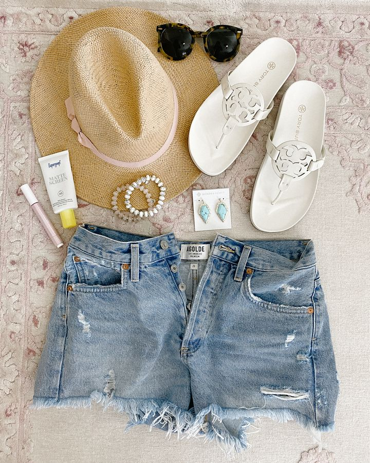 flatlay of Tory Burch Miller Cloud Sandals, hat, makeup, shorts, and accessories